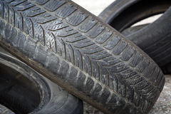 Old erased tires heaped. On concrete plates Royalty Free Stock Photo