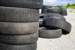 Old erased tires heaped. On concrete plates stock images