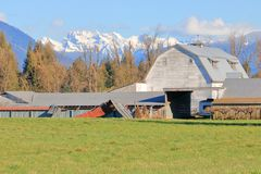 Old Established Canadian Farm and Buildings. An old established farm with various buildings, including a large barn, with scenic snow capped mountains in a rural royalty free stock photos