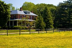 Old estate home in spring. A view across a field of yellow buttercups to a stately old brick estate home with a large porch Stock Photos