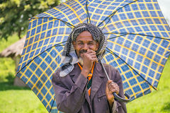 Old ethiopian man with an umbrella on a hot day Royalty Free Stock Image