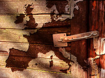 Old Map of Europe. Old outline map of Europe superposed on wooden boards in dark brown color inside a shed (or on a fence) with rusty primitive lock Royalty Free Stock Image