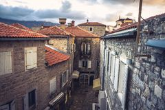 Vintage european city street  with orange tile roofs and ancient building facade in front of dramatic sunset sky with antique arch Royalty Free Stock Image