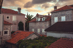 Old European city street view with orange tile roofs in antique architecture  during beautiful sunset in retro vintage style Stock Images