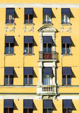 Old european yellow facade. Old yellow facade with blue awnings Stock Photo