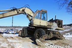 Old excavator. On winter road Stock Photos