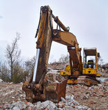 Old excavator on the ruins of an old house. Royalty Free Stock Photo