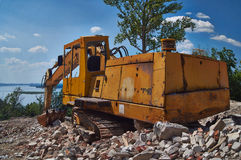 Old excavator on the ruins of an old house. Royalty Free Stock Photos