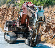 Old excavator stays near rock on Crete island Royalty Free Stock Photography