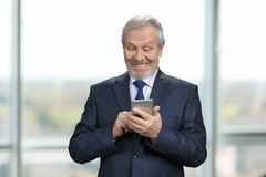 Old excited businessman with smartphone. Senior ma in suit and phone gadget. Bright blurred windows background Stock Photography