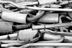 Old exhaust pipes. Pile of old exhaust pipes from cars. Black and white photo Stock Image