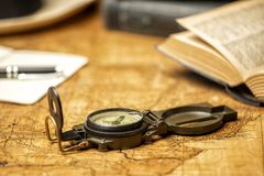 Old map with compass with notebooks and books. Old expedition map with compass notebook, books and panama hat stock image