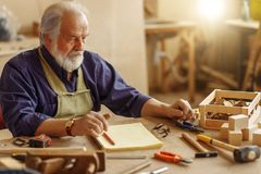 Old experienced carpenter sitting at the messy table at workplace. Close-up side view image stock photos