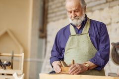 Old experienced carpenter working with wooden planer on plank workshop. Old experienced carpenter working with wooden planer on plank in workshop stock image