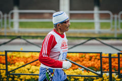 Old extravagant man runs by distance Royalty Free Stock Photo