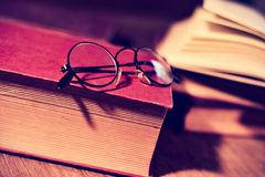 Old eyeglasses and books, filtered. Closeup of a pair of retro round-framed eyeglasses and some old book on a rustic wooden table, with a filter effect royalty free stock photos