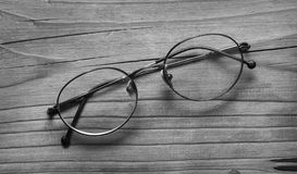 Old eyeglasses on wooden table - black and white stock photo