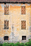 Old facade. Old weathered facade of a residential structure. Piedmont. Italy Royalty Free Stock Photo
