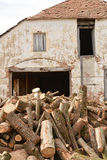 Old facade of a building ruined with stack of trunk tree near he Royalty Free Stock Photos