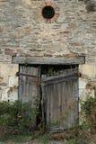 Old Facade with rustic brickwork, broken wooden door. Overgrown and grungy royalty free stock photography
