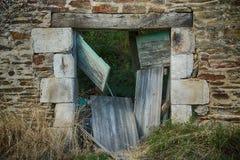 Old Facade with rustic brickwork, broken wooden door. Overgrown and grungy stock photos