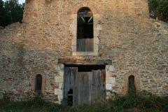 Old Facade with rustic brickwork, broken wooden door. Overgrown and grungy stock photography