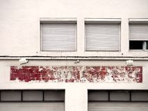 Old facade with a shabby red color, windows Stock Images