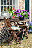 Old facade with two wooden chairs and a table Royalty Free Stock Image