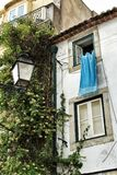 Old facade of typical Lisbon house with hanging clothes. In clothesline Royalty Free Stock Images