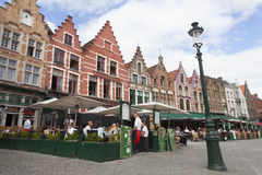 Old facades on markt in belgian city of bruges with outdoor cafe Stock Photos