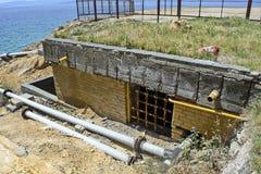Old facility coast. Old devastated facility on the seashore royalty free stock photos
