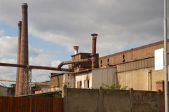 Old factory. Old fenced plant area with abandoned buildings Stock Photo