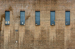 Old factory brick wall. Five windows, some of them broken Stock Image