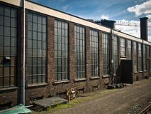 Old Factory Building. Factory building against a bright blue cloudy sky Royalty Free Stock Photos