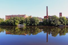 The old factory buildings among the trees with a reflection in the river. Old factory buildings among trees with reflection in the water on the river bank Stock Photography