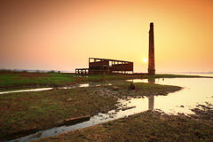 Old factory. Old decaying factory building with reflections in lake Royalty Free Stock Images