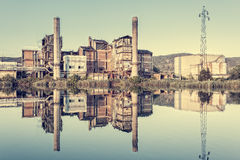 Old factory. Photo in vintage styles. Old factory that is reflected in the river.Photo in vintage styles royalty free stock photography