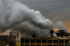 Old factory polluting the atmosphere with smoke and smog Stock Photos