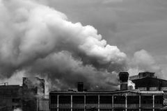 Old factory polluting the atmosphere with smoke and smog Stock Image