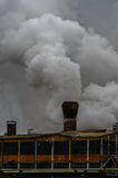Old factory polluting the atmosphere with smoke and smog Stock Photography