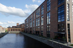 Old factory's buildings region by the river Stock Photos