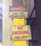 Old factory signs. No smoking, and caution signs on the old abandoned Stock Photos