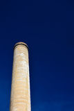 Old Factory Smokestack on a Clear Sunny Day with Blue Skies Royalty Free Stock Image