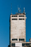 Old factory tower. Old building with new telecommunication antennas Stock Photography