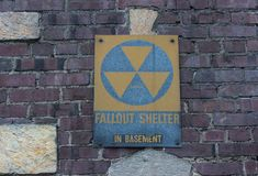 Fallout shelter sign on grungy faded wall. Old faded fallout shelter sign on grungy red brick wall background Royalty Free Stock Image