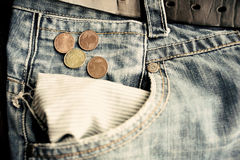 Old faded jeans with euro coins in empty pocket. Old faded jeans with euro coins near empty pocket Royalty Free Stock Photography