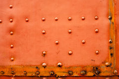 Old faded red metal background with studs Royalty Free Stock Images