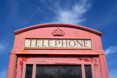 Old faded red telephone. Royalty Free Stock Photos