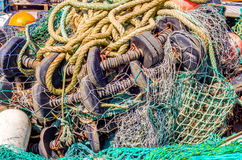 Old faded rope lying on the shore in a fishing port, industry eq Royalty Free Stock Photography