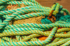Old faded rope lying on the shore in a fishing port, industry eq Stock Image